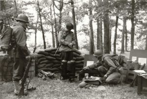 1993 Reenactment of Ardens Offensive, Belgium WWII. Note the interesting amount of period correct gear. One flamethrower is EC Brown, with more dome tank tops and the other is a Beattie Co with the flatter tops. Spare parts include:regulator new in box, safety valve and pressure bottle. Also in the photo are the original shipping crates, pack board for carrying a jerry can of fuel and the service kit. Photo from the author's collection, author right.